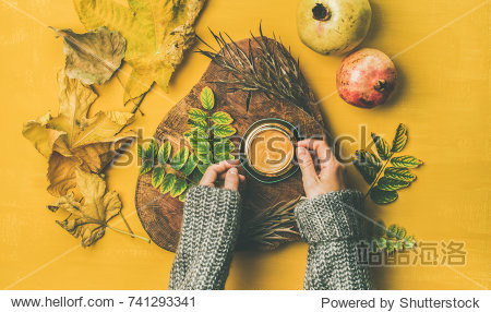 Autumn morning coffee concept. Flat-lay of woman' s hands in grey woolen sweater holding cup of espresso over mustard yellow background with dried fallen leaves and fresh pomegranates around  top view
