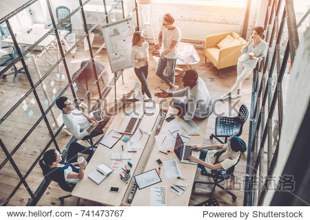 Top view of multiracial young creative people in modern office. Group of young business people are working together with laptop  tablet  smart phone  notebook. Successful hipster team in coworking.