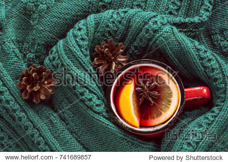 Christmas and winter traditional hot beverage. Mulled wine in red mug with spice wrapped in warm green scandinavian sweater.