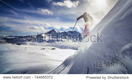 Free ride skier  skiing down steep slope  good background with blue skies and mountains