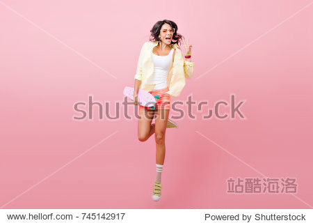 Full-length portrait of adorable hispanic female model in denim shorts having fun in studio with pink interior. Photo of jumping brunette lady in yellow jacket holding skateboard.