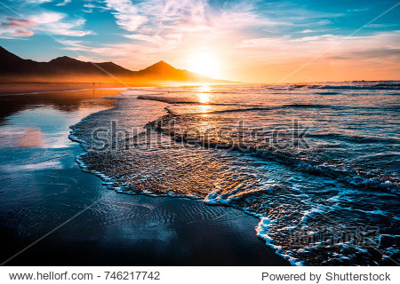 Amazing beach sunset with endless horizon and lonely figures in the distance  and incredible foamy waves. Volcanic hills in the background.