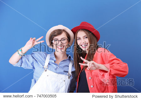 Attractive hipster girls posing on color background