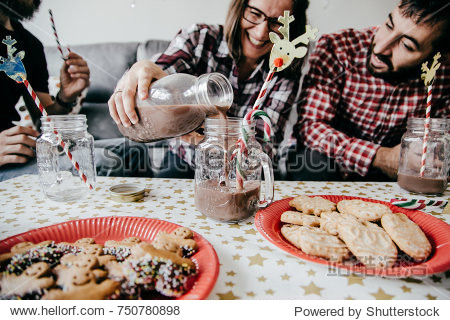 A group of happy friends having a nice Christmas afternoon  drinking chocolate and eating Christmas cookies. Lifestyle photography