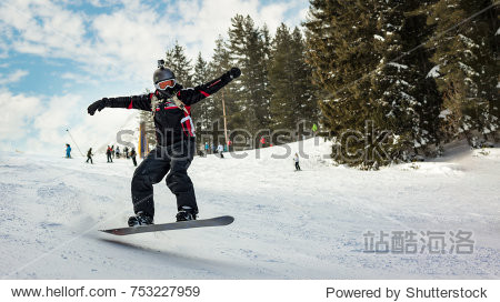 Snowboarder jumps on mountain slopes and enjoying a sunny winter day.