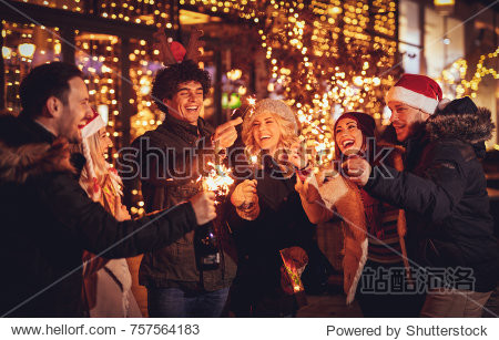 Three couple with sparklers enjoying Christmas outdoor party in the city street at night and with a lot of lights on background.