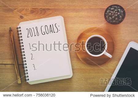 Top view 2018 goals list with notebook  cup of coffee on wooden desk