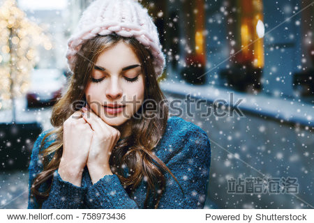 Outdoor close up portrait of young beautiful girl with long hair wearing hat  sweater posing in street of european city.  Christmas  winter holidays concept. Snowfall. Copy  empty space for text