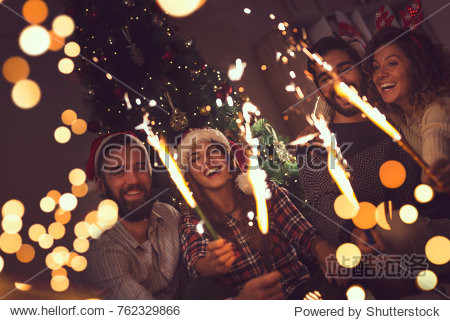Group of young friends having fun at a New Year's celebration  holding sparklers at a midnight countdown.