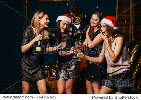 Happy smiling girls In stylish glamorous outfit with champagne glasses at Christmas party.