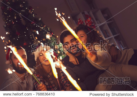 Group of young friends having fun at a New Year's celebration  holding sparklers at a midnight countdown. Focus on the guy on the right