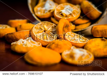 Dried squeezed lemons Citrus × limon in a rusted bowl on wooden surface.