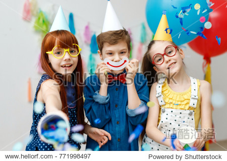 Three friendly children in festive cone caps and big eyewear  stand in decorative room with balloons  have fun together as celebrate birthday look with happy expressions at camera  enjoy playing games