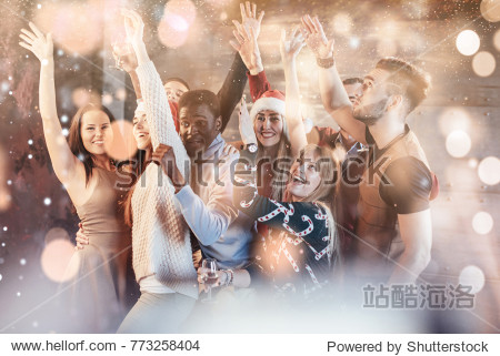 Party with friends. They love Christmas. Group of cheerful young people carrying sparklers and champagne flutes dancing in new year party and looking happy. Bokeh light soft effect.