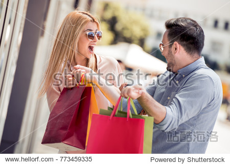 Stylish young couple doing shopping in the city they holding shopping bags.