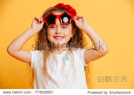 Photo of little cute pretty girl standing isolated over yellow background wearing sunglasses looking camera.