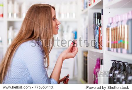 Beautiful customer woman at beauty store choosing lip gloss  cosmetic shopping