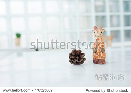 Cute animal doll : giraffe with pine cones on marble table