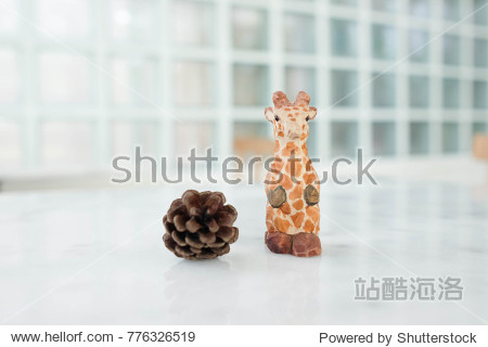 Cute animal doll : close up giraffe with pine cones on marble table