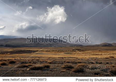 Dramatic fall dark desert steppe on a highland mountain plateau with ranges of hills on a horizon storm skyline Kurai Altai Mountains Siberia Russia