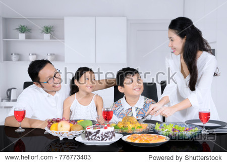 Picture of young mother serving a roast chicken for her husband and children while having dinner together at home