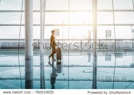 Young lovely curly African American student girl in warm clothes and with a huge rolling bag is waiting her flight next to big glass facade of modern airport or depot terminal with teal reflections