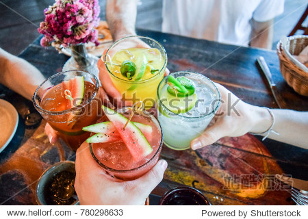 Friends toasting  saying cheers holding tropical blended fruit margaritas.  Watermelon and passionfruit drinks.