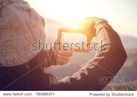 Future planning  Close up of woman hands making frame gesture with sunrise on mountain  Female capturing the sunrise  sunlight outdoor.