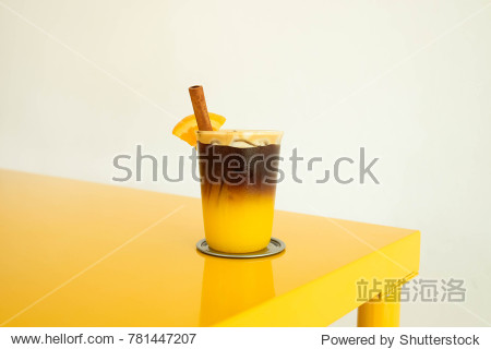 Yellow color background concept : a layer of ice espresso and orange juice decorate with cinnamon on yellow table  white wall for copy space