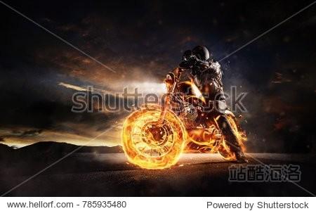 Dark motorbiker staying on burning motorcycle in sunset light. Dark art wallpaper photo of chopper motorbike. Very high resolution image