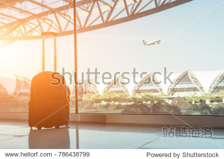 Silhouette of luggage or suitcase placed at the window at waiting terminal in international airports in Thailand with the airplan taking off behide the building.