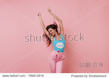 Lovely slim girl posing with sincere smile. Pretty long-haired female model dancing with hands up on pink background.