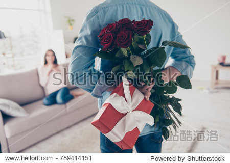 Unexpected moment in routine everyday life! Cropped photo of man's hands hiding holding chic bouquet of red roses and gift with white ribbon behind back  happy woman is on blurred background