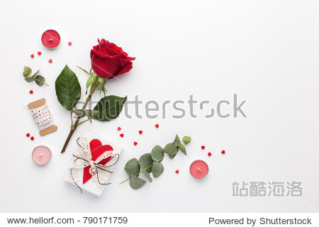 Frame made of rose flower  gift and candles on white background. Flat lay  top view  copy space.