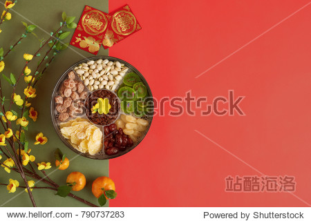Box with sweet snacks  blooming apricot branches and lucky envelops with best wishes inscription on green and red background
