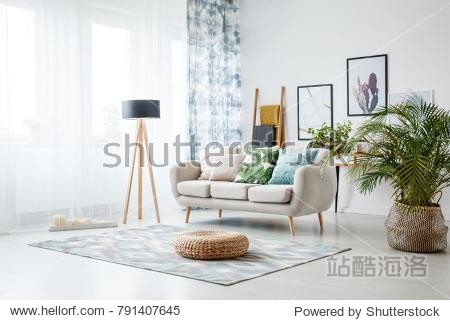 Black lamp standing by a sofa and a row of candles lying on the floor in front of a window shedding light on the interior of boho style living room