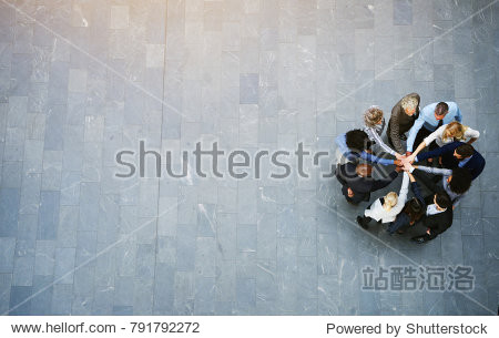 High angle view of a team of united businesspeople standing with their hands together in a huddle in the lobby of a modern office building