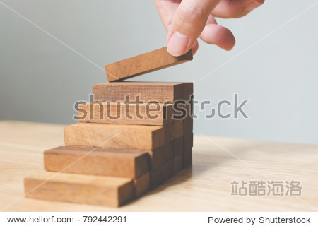 Hand arranging wood block stacking as step stair. Ladder career path concept for business growth success process  Copy space