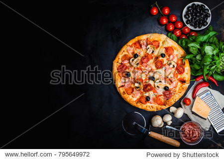 Traditional Italian pizza  vegetables  ingredients on a dark metallic background. Pizza is cooking in the oven. Pizza menu. View from above. Space for text.