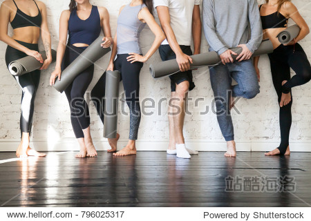 Group of young sporty people standing at wall. Students taking a rest from fitness activity  time to recover strength  waiting for a lesson to start in loft studio  close up. Healthy lifestyle concept