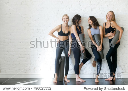 Group of young sporty girls with yoga mats standing at white wall. Female companions in gym resting after fitness  indoor full length  loft studio  copy space