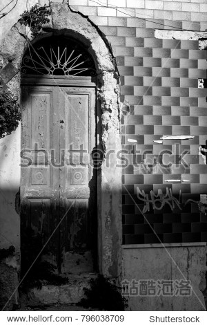Ruined and Broken Facade With a Closed Old Wooden  Door  in Black and White