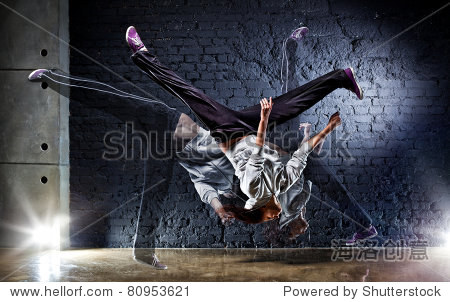 Young woman dancer on wall background.