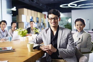 a team of young asian entrepreneurs posing in meeting room.