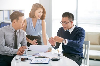 Asian businessman talking to coworkers about his project