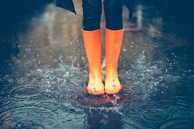 Feeling protected in her boots. Close-up of woman in orange rubber boots jumping on the puddle