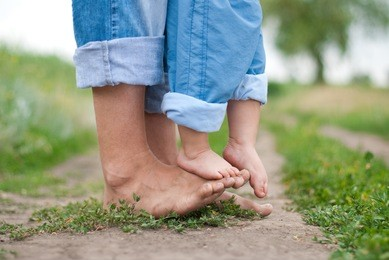 Happy Family on a Walk in Summer. Child with Father Together. Feet Barefoot on Green Grass. Healthy Lifestyle. Dad and Son. Spring Time.