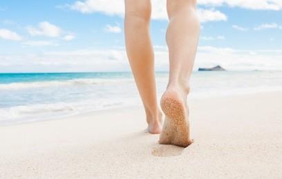Woman walking on white sand beach in Hawaii.
