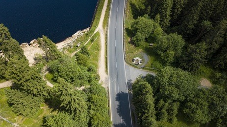 Drone photography with a street crossing the harz national park at the edge of a mountain lake surrounded by fir trees.