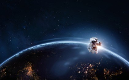 Astronaut in outer space over of the planet earth at the night hemisphere. Science theme. Astronomy concept. Elements of this image furnished by NASA.